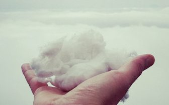 A hand holding a ball of snow that looks like a cloud