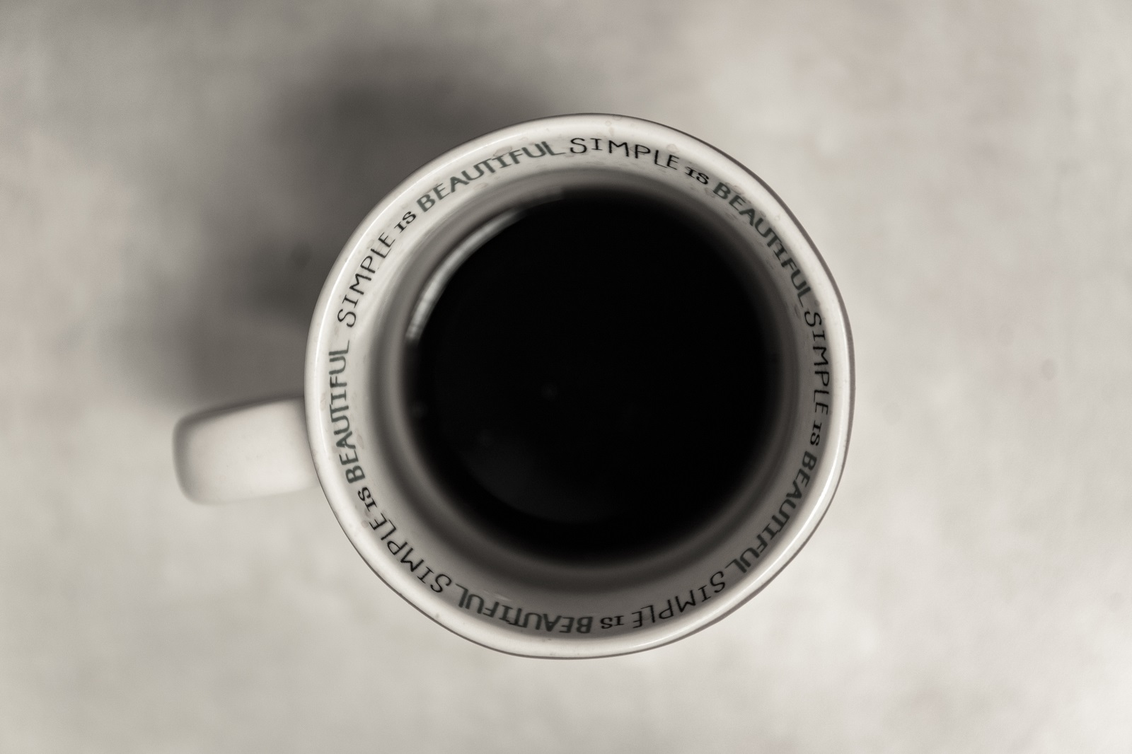"A mug with the text ""simple is beautiful"" written on the rim"