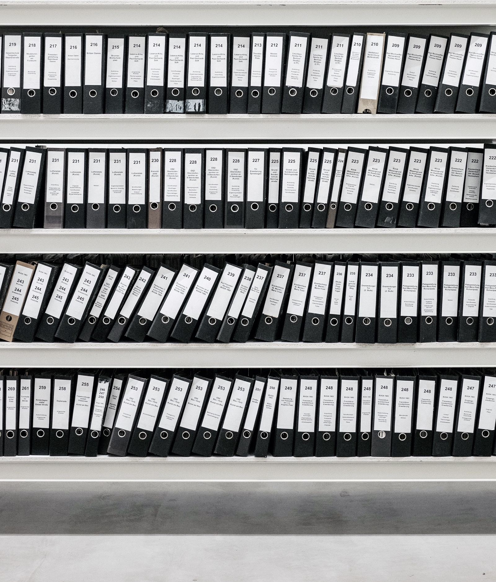 A photo of rows of black binders representing document management