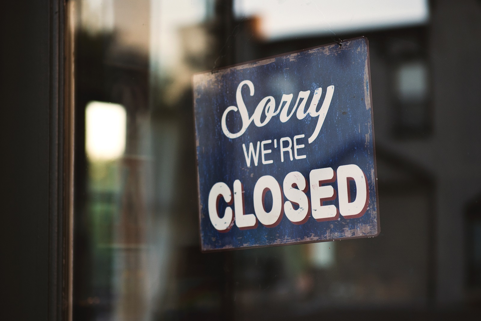 "A photo of a sign through a window that says ""Sorry we're closed"""