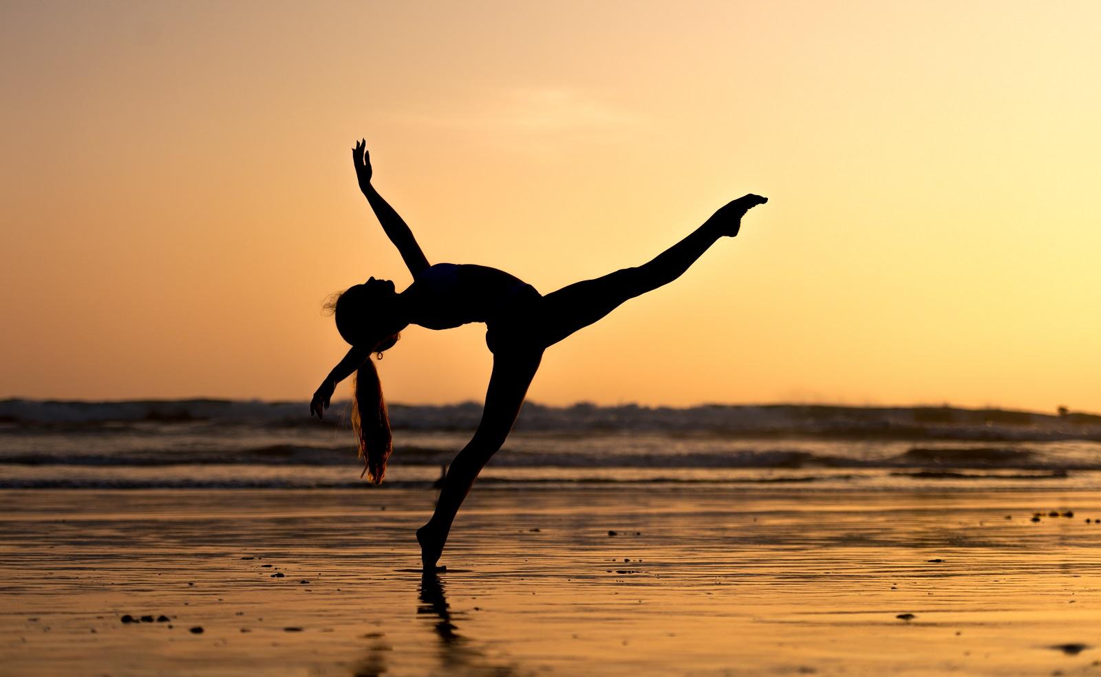 a photo of a girl doing yoga on the beach